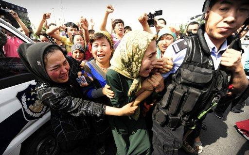 Uighur protestors dragged away by Han police officers