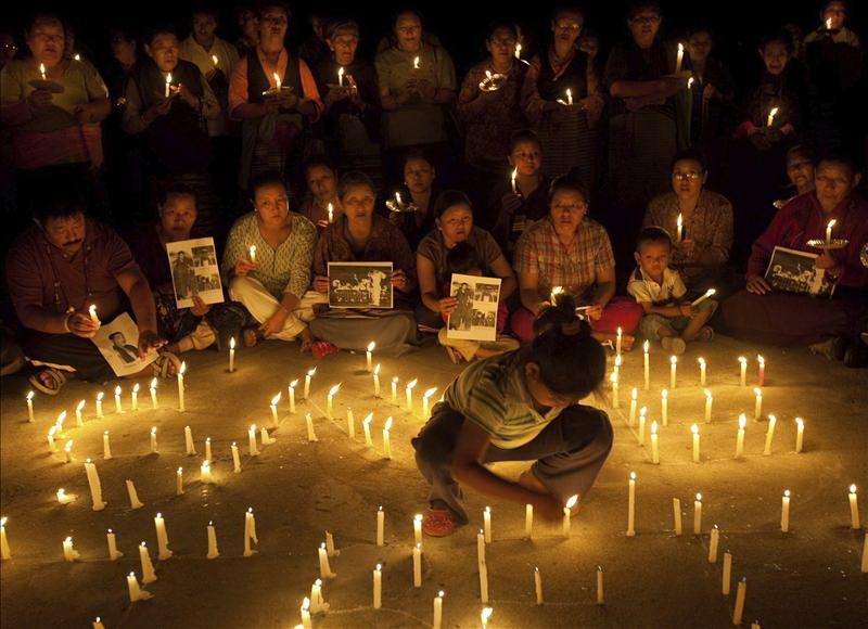 Tibetans hold a candlelight vigil